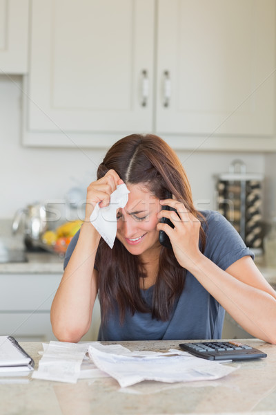 Woman holding a bill to her head while calling Stock photo © wavebreak_media