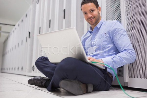 Man working on laptop connected to server in data center Stock photo © wavebreak_media