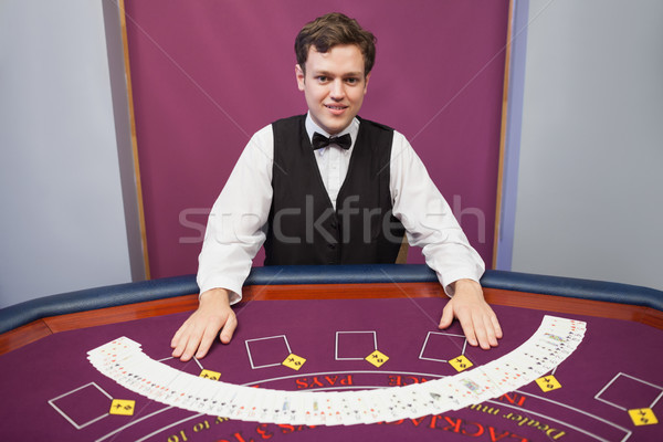 Smiling dealer with fanned out deck of cards in casino  Stock photo © wavebreak_media