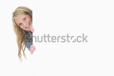 Blue-eyed woman hiding behind a poster while smiling Stock photo © wavebreak_media
