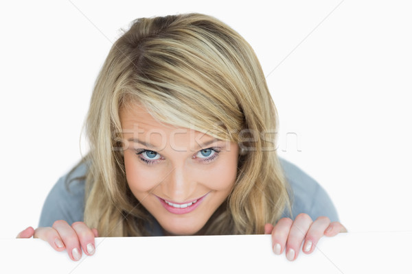 Blonde woman holding a notice while hiding behind it Stock photo © wavebreak_media