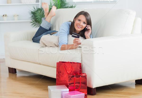 Foto d'archivio: Donna · divano · carta · di · credito · chiamando · soggiorno