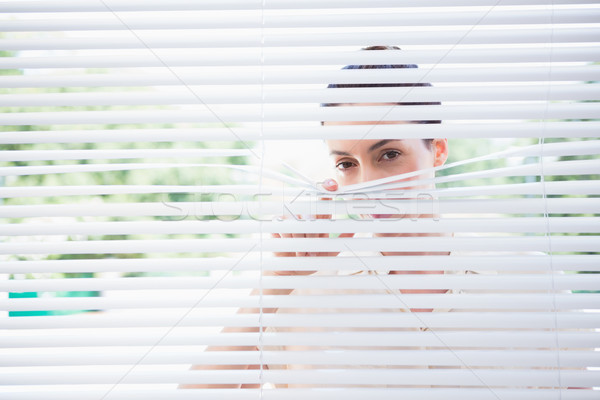 Woman peeking through blinds Stock photo © wavebreak_media