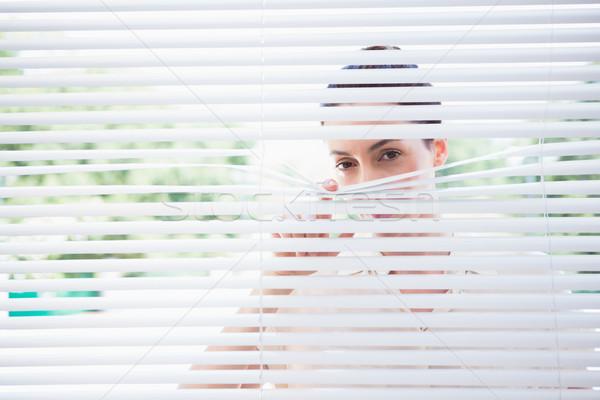 Stock photo: Woman peeking through blinds