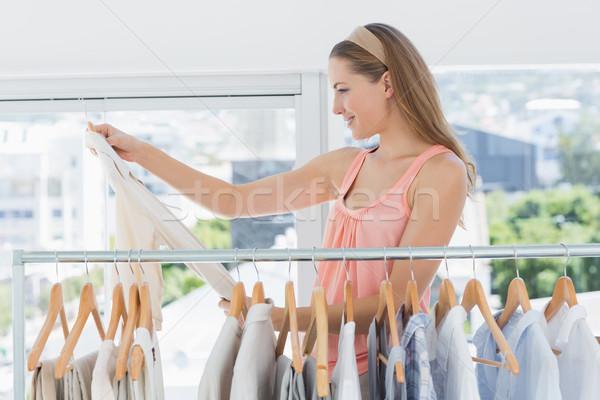 Femminile moda designer guardando shirt rack Foto d'archivio © wavebreak_media