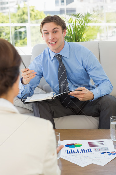 Happy businessman scheduling with colleague sitting on sofa Stock photo © wavebreak_media