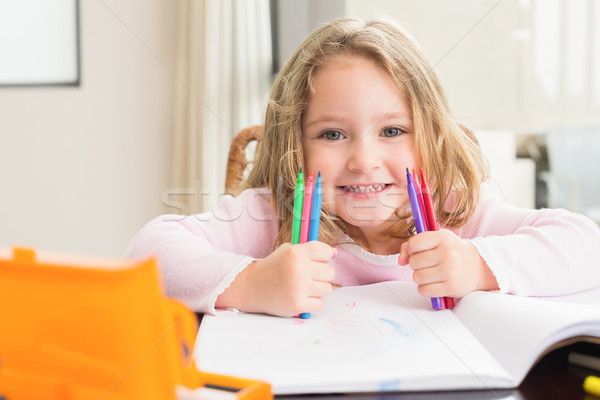 Cheerful little girl colouring at the table Stock photo © wavebreak_media