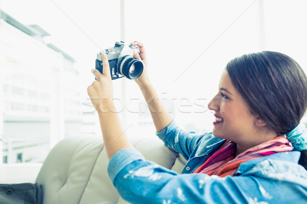 Young brunette sitting on sofa taking a selfie  Stock photo © wavebreak_media