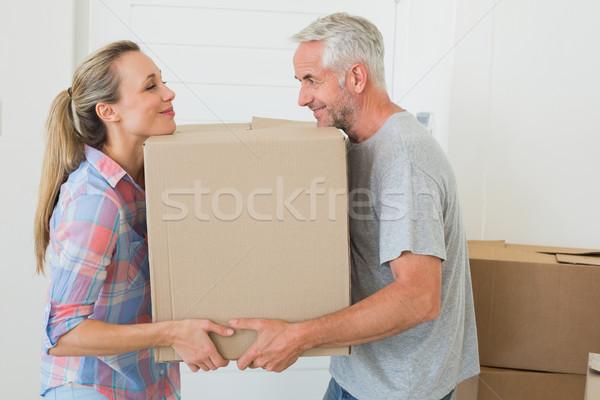 Happy couple carrying cardboard moving boxes  Stock photo © wavebreak_media
