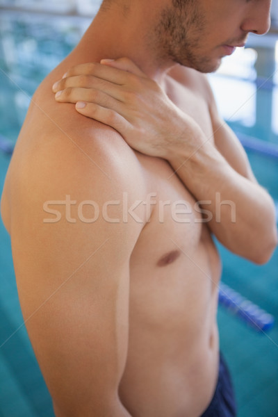 Fit swimmer standing by the pool touching his shoulder Stock photo © wavebreak_media