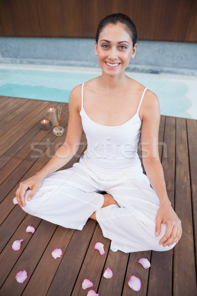 Peaceful brunette in white sitting in lotus pose surrounded by p Stock photo © wavebreak_media