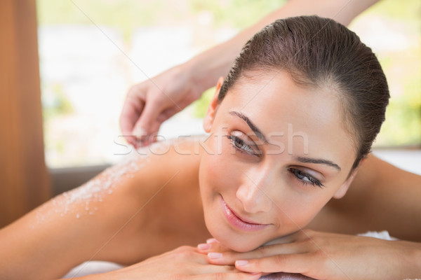 Stock photo: Beauty therapist pouring salt scrub on smiling womans back