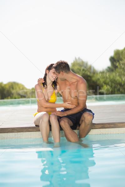 Gorgeous couple sitting poolside on holidays Stock photo © wavebreak_media