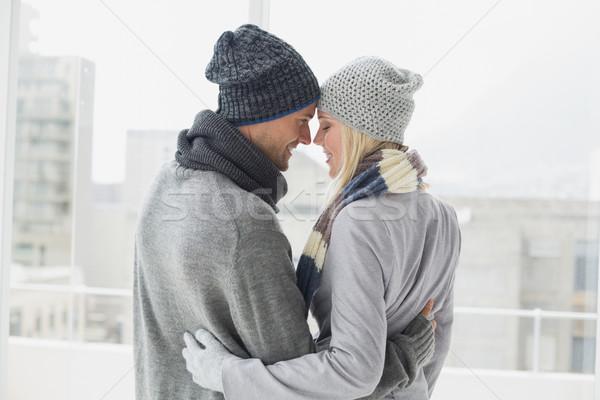 Cute couple in warm clothing hugging Stock photo © wavebreak_media