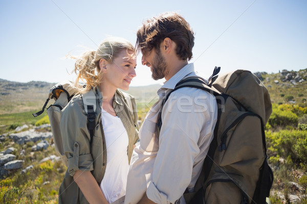 Hiking couple standing on mountain terrain smiling at each other Stock photo © wavebreak_media