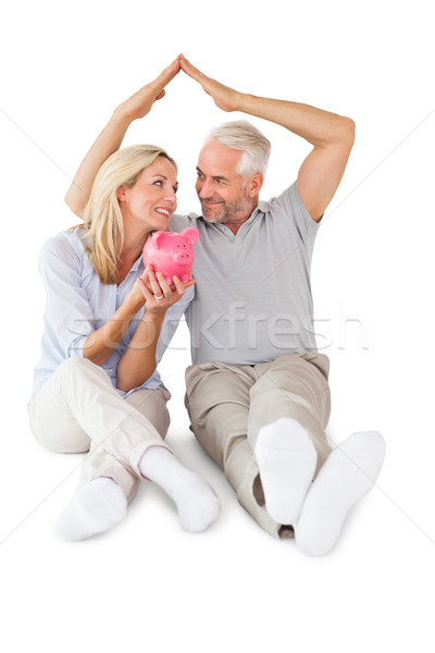 Happy couple sitting and sheltering piggy bank Stock photo © wavebreak_media