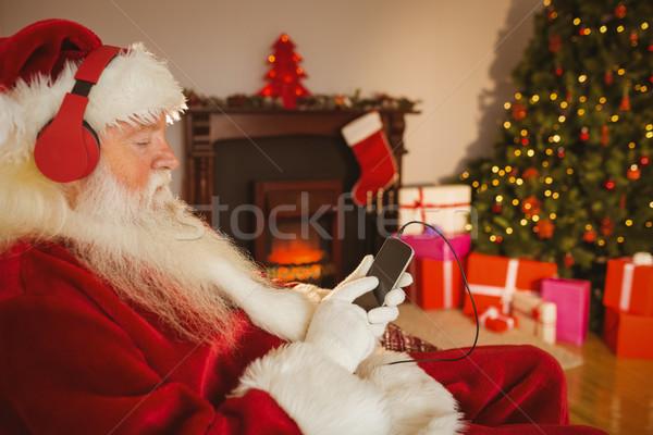 Święty mikołaj słuchania muzyki smartphone domu salon Zdjęcia stock © wavebreak_media