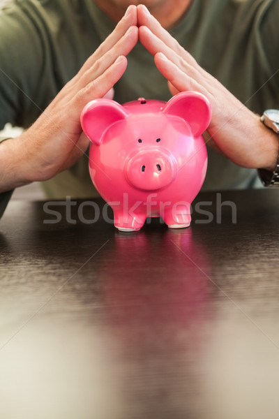 Mid section of a man with joined hands on piggy bank Stock photo © wavebreak_media