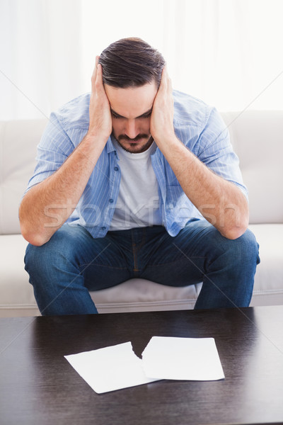 Upset man sitting head in hands on couch Stock photo © wavebreak_media