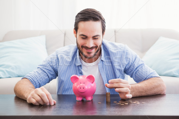 Smiling businessman putting coins into piggy bank Stock photo © wavebreak_media