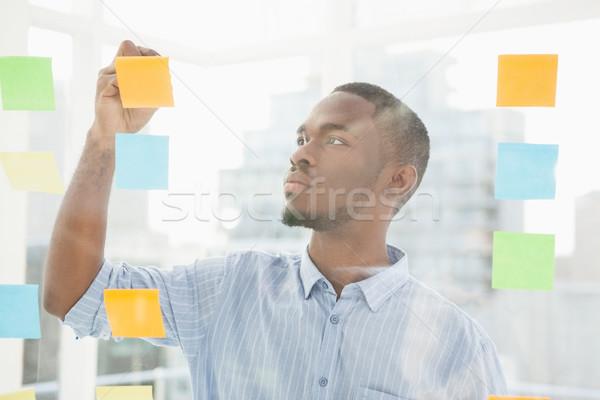 Figyelmes üzletember ír cetlik ablak iroda Stock fotó © wavebreak_media