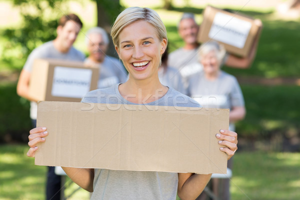 Happy volunteer blonde holding blank Stock photo © wavebreak_media