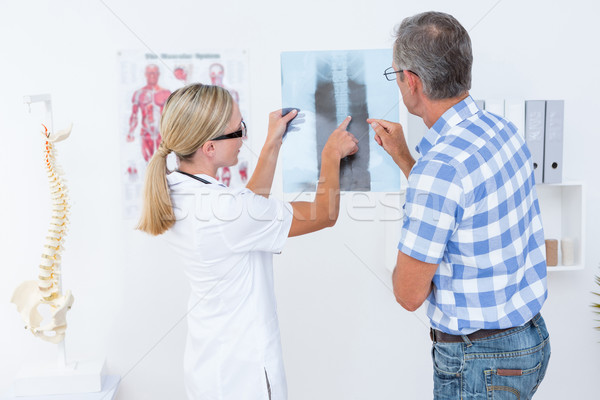 Doctor showing X rays to her patient  Stock photo © wavebreak_media
