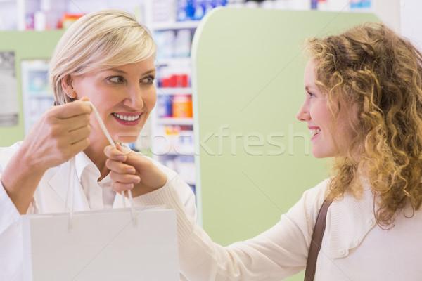 Pharmacist and costumer holding paper bag  Stock photo © wavebreak_media