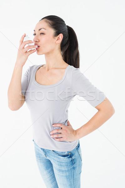 Asthmatic pretty brunette using inhaler  Stock photo © wavebreak_media