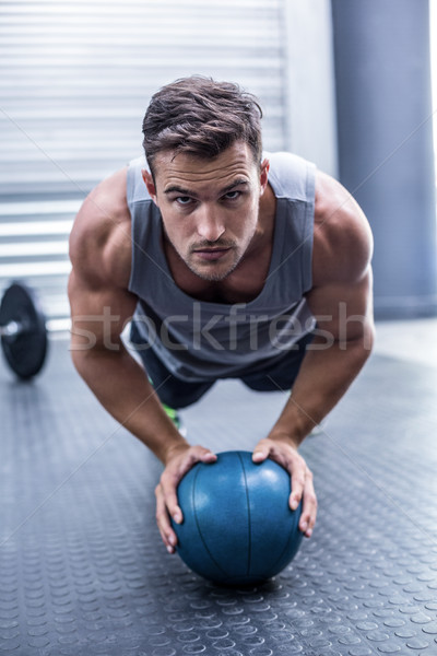 Muscular man on a plank position with a ball  Stock photo © wavebreak_media