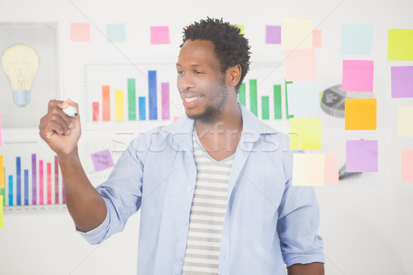 Casual businessman looking at post-it Stock photo © wavebreak_media