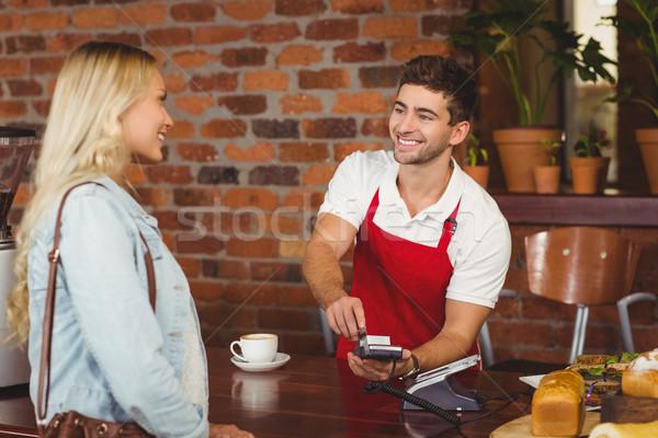 Smiling waiter using the pin terminal  Stock photo © wavebreak_media