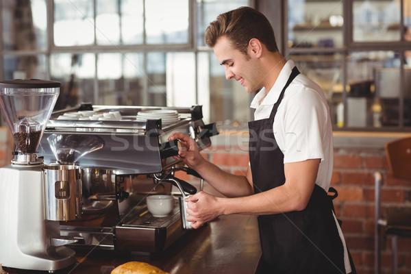 Smiling barista steaming milk at coffee machine Stock photo © wavebreak_media