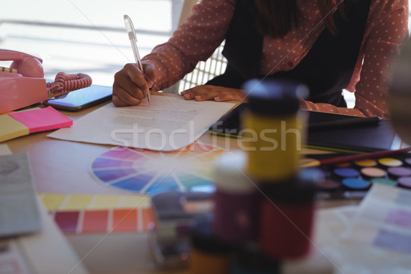 Mid section of businesswoman writing on paper at office desk Stock photo © wavebreak_media