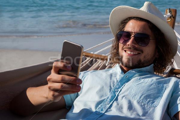 Férfi megnyugtató függőágy mobiltelefon tengerpart mosolyog Stock fotó © wavebreak_media