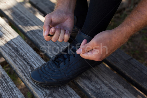 Player tying shoes on wooden bench Stock photo © wavebreak_media