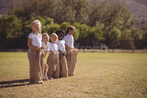 Portrait of happy schoolgirls standing in sack during race Stock photo © wavebreak_media