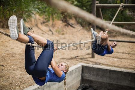 Trainer assisting a boy in obstacle course training Stock photo © wavebreak_media