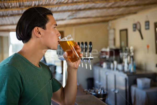Young man drinking beer Stock photo © wavebreak_media