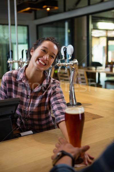 Happy barmaid serving drink to man Stock photo © wavebreak_media