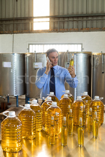 Manager talking on mobile phone while examining olive oil Stock photo © wavebreak_media