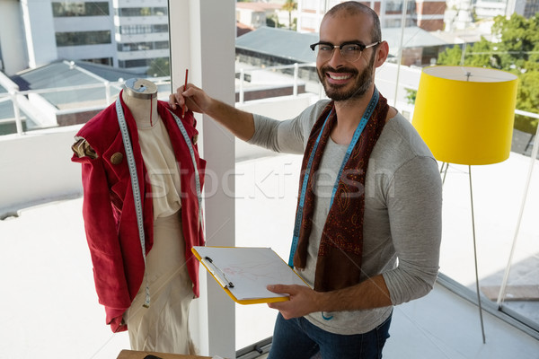 Portrait of smiling designer holding clipboard standing by mannequin Stock photo © wavebreak_media