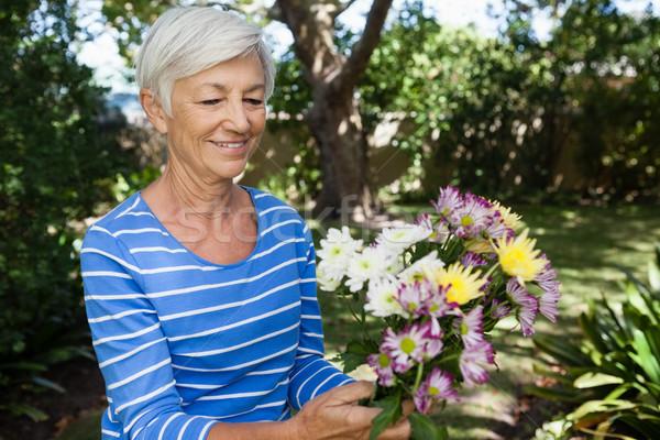 Smiling senior woman holding fresh flower bouquet Stock photo © wavebreak_media