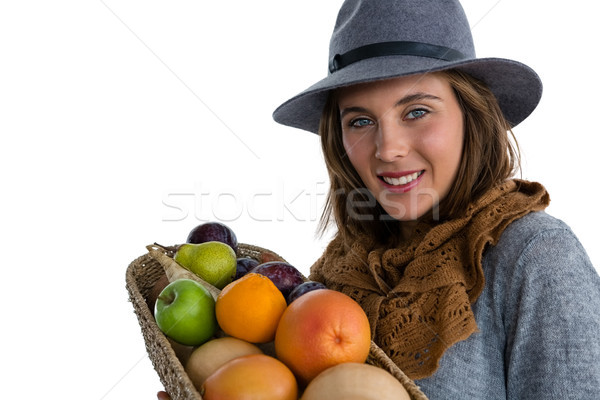 Portrait of smiling woman carrying fruits and vegetables in basket while standing against white back Stock photo © wavebreak_media