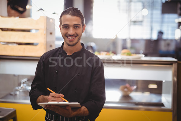 Portrait of smiling young waiter holding clipboard Stock photo © wavebreak_media
