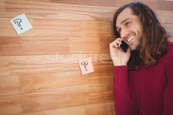 Gelukkig man mobiele telefoon houten muur Stockfoto © wavebreak_media