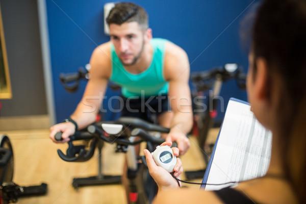 Entrenador sincronización hombre ejercicio moto gimnasio Foto stock © wavebreak_media