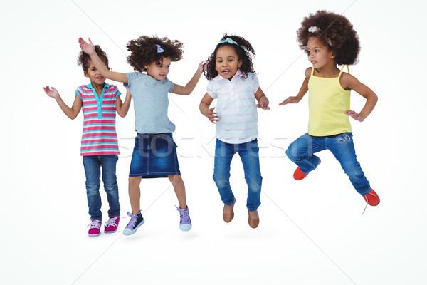 Aranyos lányok ugrik fehér képernyő boldog Stock fotó © wavebreak_media
