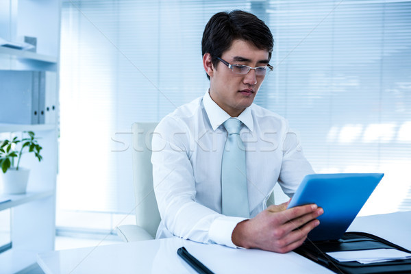 Serious asian businessman using his tablet Stock photo © wavebreak_media