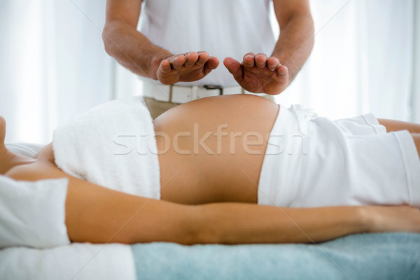 Pregnant woman receiving a stomach massage from masseur Stock photo © wavebreak_media